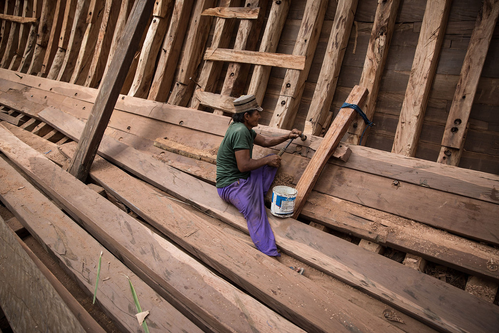 . A Buginese man installs a wooden block to finish the hull of phinisi at Tanjung Bira Beach on May 2, 2014 in Bulukumba, South Sulawesi, Indonesia.  (Photo by Agung Parameswara/Getty Images)