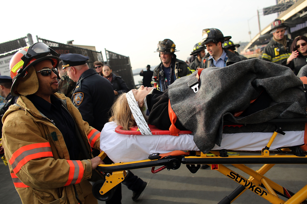 . An injured woman is carried to a waiting ambulance following an early morning ferry accident during rush hour in Lower Manhattan on January 9, 2013 in New York City. About 50 people were injured in the accident, which left a large gash on the front side of the Seastreak ferry at Pier 11.  (Photo by Spencer Platt/Getty Images)