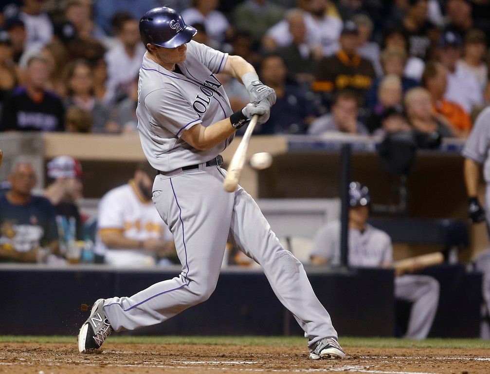. Colorado Rockies\' DJ LeMahieu hits an RBI single against the San Diego Padres in the fourth inning of a baseball game Tuesday, Sept. 23, 2014, in San Diego.  (AP Photo/Lenny Ignelzi)
