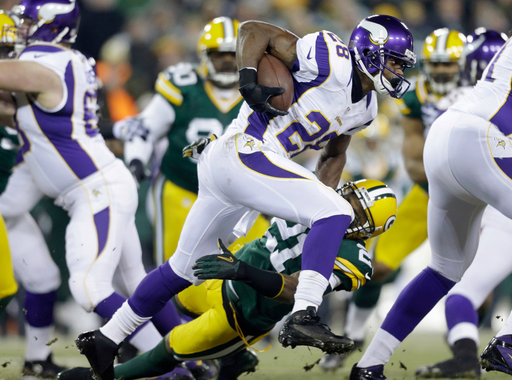 Description of . Minnesota Vikings running back Adrian Peterson (28) tries to break a tackily by Green Bay Packers strong safety Charles Woodson (21) during the first half of an NFL wild card playoff football game Saturday, Jan. 5, 2013, in Green Bay, Wis. (AP Photo/Jeffrey Phelps)