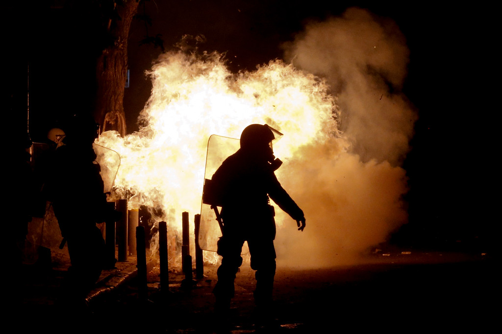 . A riot policeman  tries to avoid a petrol bomb thrown by protesters during clashes in the Athens neighborhood of Exarchia, a haven for extreme leftists and anarchists, on Saturday, Dec. 6, 2014.  (AP Photo/Petros Giannakouris)
