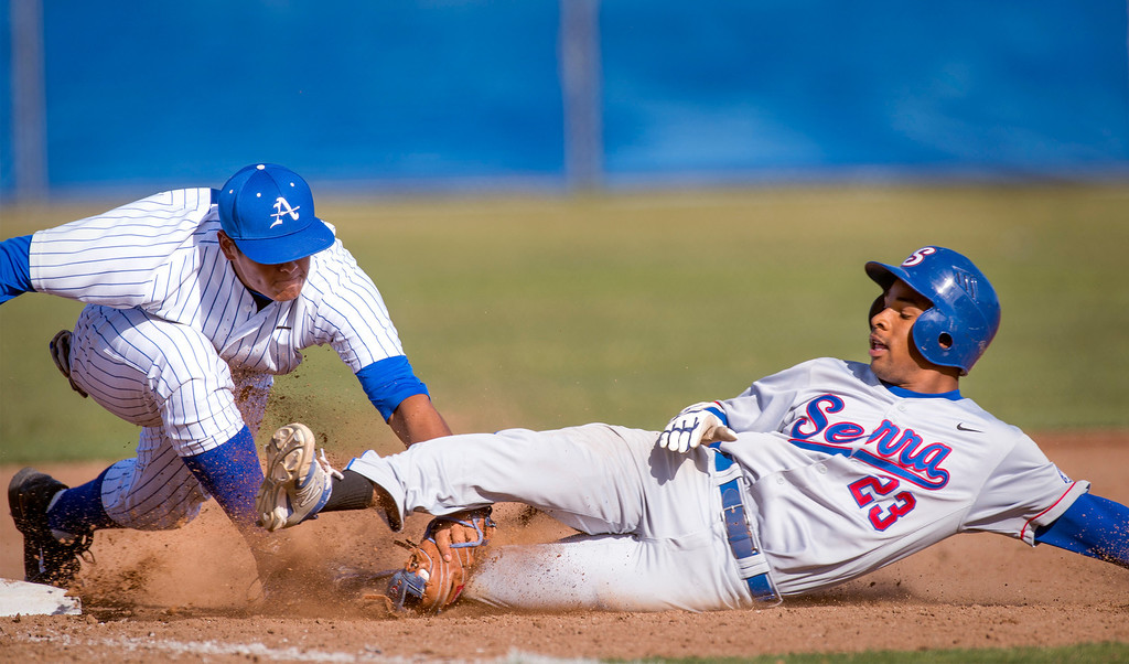 . Bishop Amat\'s 3B Jayson Gonzalez, left, tags out Serra High\'s Denz\'l Chapman trying to stretch a triple in the sixth inning at Amat\'s La Puente, Calif. campus field April 16, 2014.  (Staff photo by Leo Jarzomb/San Gabriel Valley Tribune)