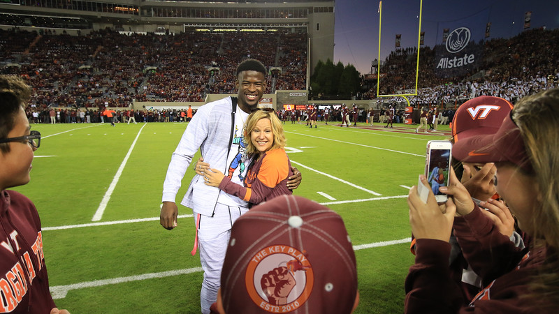 Former Virginia Tech and current NFL wide receiver Isiaiah Ford takes photos with fans on the sidelines during warmups. (Mark Umansky/TheKeyPlay.com)