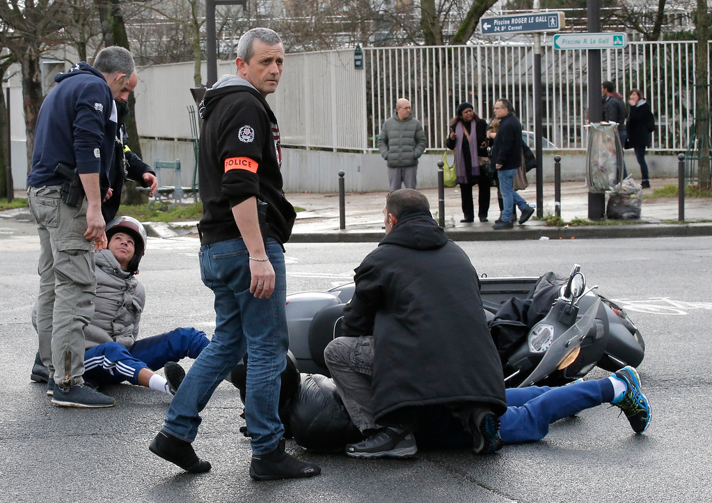 . Police officers detain youth who riding a scooter outside a hostage-taking situation at a kosher market in Paris, Friday Jan.9, 2015. France\'s anti-terrorism prosecutor says a shooting and hostage-taking attack is underway at a kosher market on the eastern edge of Paris. A police official said there are multiple hostages and wounded at the scene.  It is not known if the two youths were involved in the hostage taking situation. (AP Photo/Francois Mori)