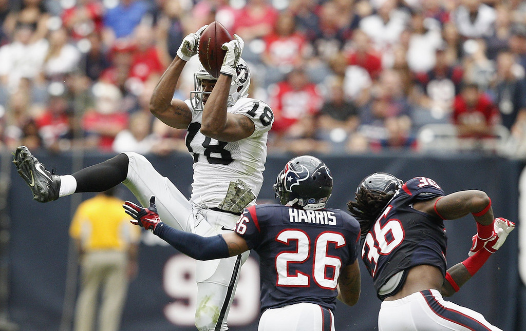 . Andre Holmes #18 of the Oakland Raiders goes up over Brandon Harris #26 and D.J. Swearinger #36 of the Houston Texans for a reception at Reliant Stadium on November 17, 2013 in Houston, Texas.  (Photo by Bob Levey/Getty Images)