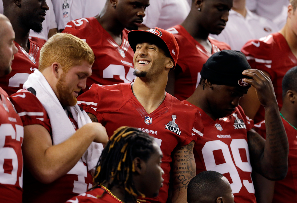 Description of . San Francisco 49ers quarterback Colin Kaepernick smiles as the team sets up for a photo during media day for the NFL Super Bowl XLVII football game Tuesday, Jan. 29, 2013, in New Orleans. (AP Photo/Mark Humphrey)