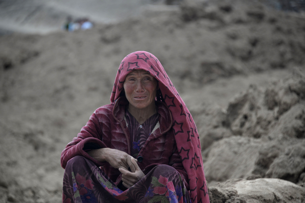 . An Afghan villager cries as she sits on top of a mud field at the scene in Argo district of Badakhshan province on May 3, 2014 after a massive landslide May 2 buried a village. Rescuers searched in vain for survivors May 3 after a landslide buried an Afghan village, killing 350 people and leaving thousands of others feared dead amid warnings that more earth could sweep down the hillside. Local people made desperate efforts to find victims trapped under a massive river of mud that engulfed Aab Bareek village in Badakhshan province, where little sign remained of hundreds of destroyed homes. (FARSHAD USYAN/AFP/Getty Images)
