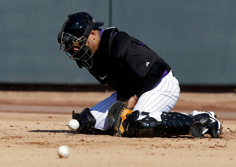 . Colorado Rockies\' Yorvit Torrealba makes a stop during a drill at spring training baseball Tuesday, Feb. 12, 2013, in Scottsdale, Ariz. (AP Photo/Darron Cummings)