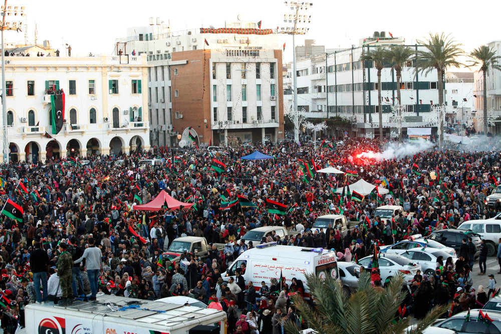Description of . People wave Libyan flags as they gather during celebrations commemorating the second anniversary of the country's February 17 revolution, at Martyrs' Square in Tripoli February 17, 2013. REUTERS/Ismail Zitouny