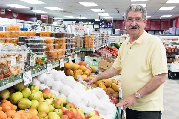 Owner Hilmi Sevimli looks over the produce at Veggie World.