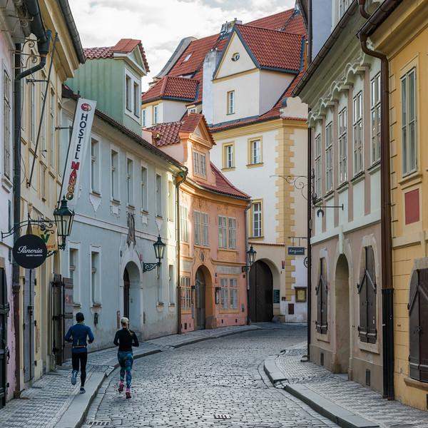 Rear view of man and woman running on a city street, Prague, Czech Republic