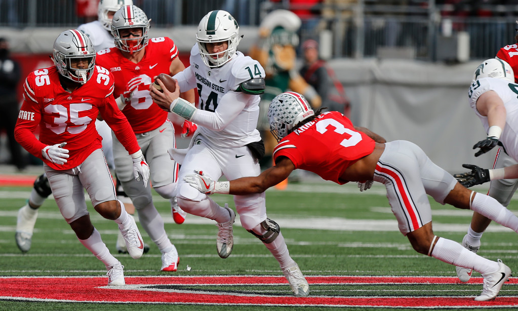 . Michigan State quarterback Brian Lewerke, center, runs the ball as Ohio State cornerback Damon Arnette, right, makes the tackle during the first half of an NCAA college football game Saturday, Nov. 11, 2017, in Columbus, Ohio. (AP Photo/Jay LaPrete)