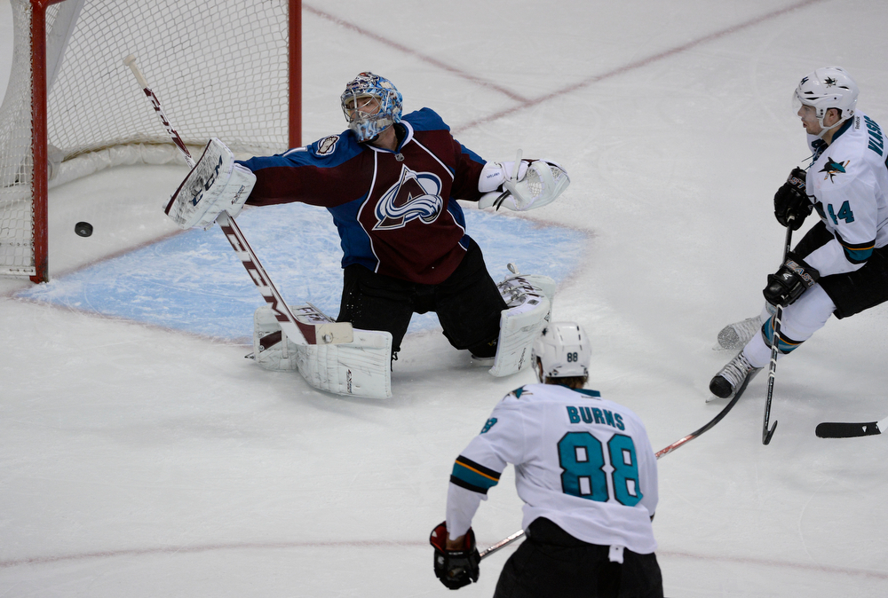 . Colorado Avalanche goalie, Semyon Varlamov, blocks a shot as San Jose Sharks defenders, Matt Nieto, bottom center, and MArc-Edouard Vlasic, converge on the net in the second period of play at the Pepsi Center Saturday afternoon, March 29, 2014. The Av\'s won 3-2 securing a playoff spot with the win. (Photo By Andy Cross / The Denver Post)