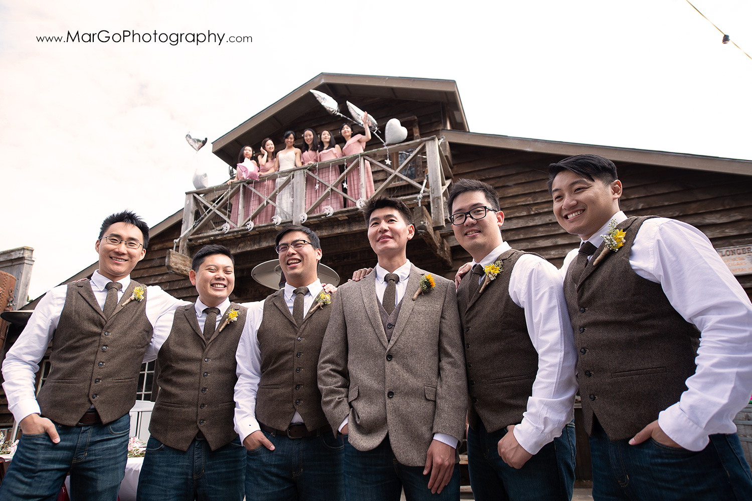 groom and groomsmen under the balcony with bride and bridesmaids in pink dresses at Long Branch Saloon & Farms in Half Moon Bay - focus on guys