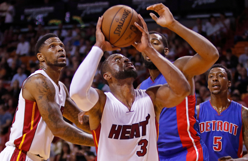 . CORRECTS DAY OF WEEK - Miami Heat guard Dwyane Wade (3) shoots as Detroit Pistons center Andre Drummond and Kentavious Caldwell-Pope (5) trail in the first half of an NBA basketball game, Sunday, March 29, 2015, in Miami. At left is Miami Heat forward Udonis Haslem. (AP Photo/Joe Skipper)