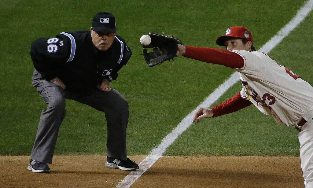 . Umpire Jim Joyce watches as St. Louis Cardinals third baseman David Freese catches a line drive hit by Boston Red Sox\'s Dustin Pedroia during the sixth inning of Game 3 of baseball\'s World Series Saturday, Oct. 26, 2013, in St. Louis. (AP Photo/David J. Phillip)