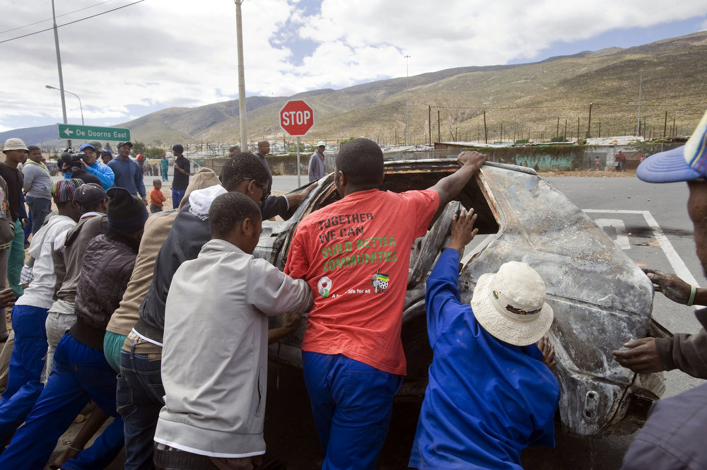 . A group of men try to roll a burnt out car onto the N1 highway, in ongoing violence during the farmworkers strike, on January 10, 2012 in de Doorns, a small farming town about 140Km North of Cape Town, South Africa. The farm workers have said that they they will not return to work on the fruit growing region\'s farms until they receive a daily wage of at least R150($17) per day, which is about double what they currently earn. One of the men wears a red t-shirt of the ruling African National Congress(ANC).  AFP PHOTO / RODGER  BOSCH/AFP/Getty Images