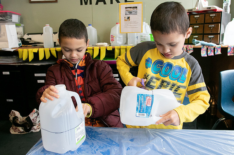 Lunenburg Public Library taught kids how to create milk jug greenhouses during their winter sowing program. Brothers Jeriel, 5, and Julian Plaza, 9, work on cutting their milk jugs as they start to create their greenhouses. SENTINEL & ENTERPRISE/JOHN LOVE