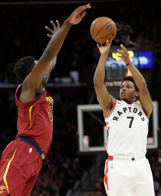 . Toronto Raptors\' Kyle Lowry, right, shoots over Cleveland Cavaliers\' Jeff Green in the first half of an NBA basketball game, Wednesday, March 21, 2018, in Cleveland. (AP Photo/Tony Dejak)