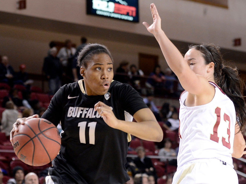 . University of Colorado\'s Brittany Wilson drives past Emiko Smith during a games against the University of Denver on Tuesday, Dec. 11, at the Magnus Arena on the DU campus in Denver.   (Jeremy Papasso/Daily Camera)