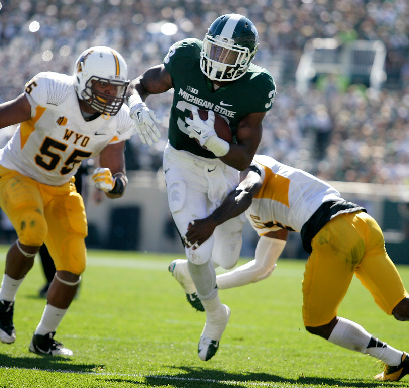 . Michigan State\'s Jeremy Langford, center, rushes against Wyoming\'s Eddie Yarbrough (55) and DeAndre Jones, right, during the second quarter of an NCAA college football game, Saturday, Sept. 27, 2014, in East Lansing, Mich. Michigan State won 56-14. (AP Photo/Al Goldis)