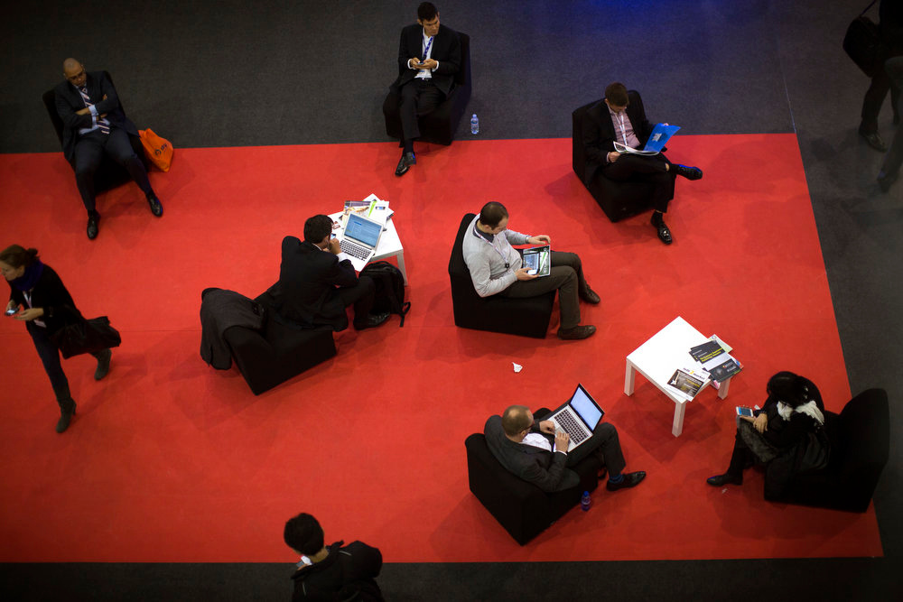 . Attendees use their devices inside a pavilion of the Mobile World Congress, the world\'s largest mobile phone trade show, in Barcelona, Spain on Tuesday, Feb. 26, 2013. (AP Photo/Emilio Morenatti)
