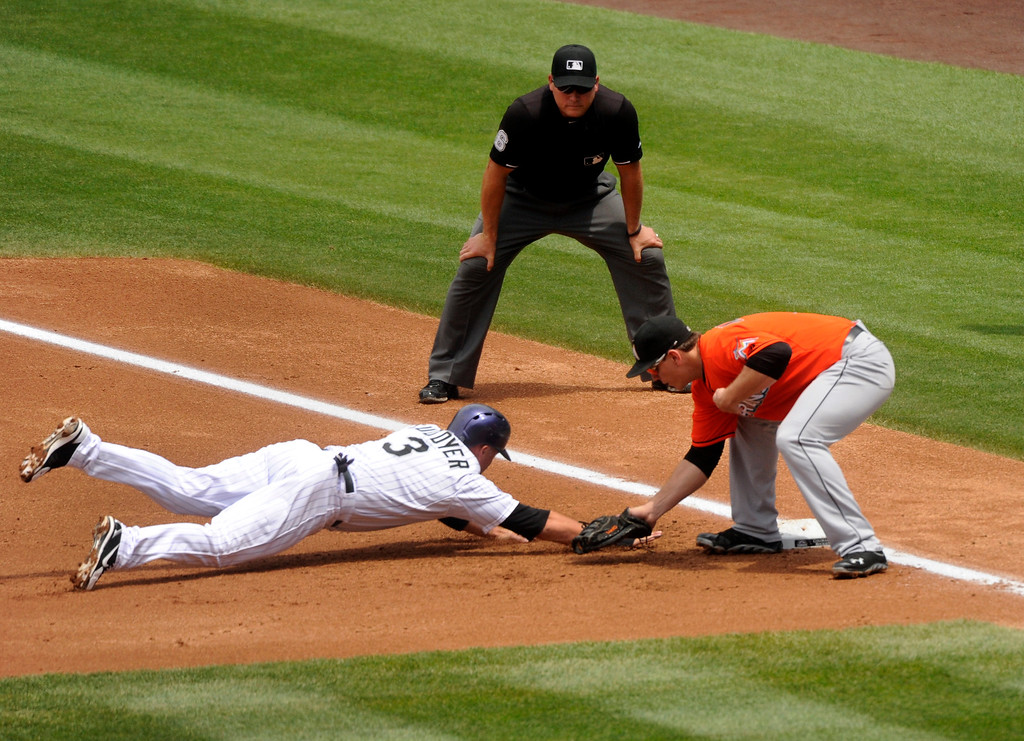 . Miami infielder Logan Morrison applied the tag to Rockies baserunner Michael Cuddyer on a pick off play at first base in the second inning. Cuddyer was called out. The Colorado Rockies hosted the Miami Marlins at Coors Field Thursday afternoon, July 25, 2013. Photo By Karl Gehring/The Denver Post