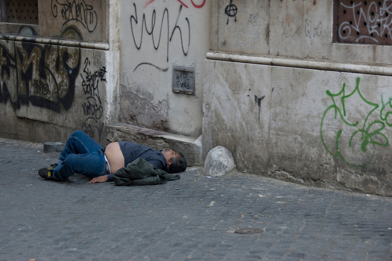 Homeless man spotted sleeping at a street in Rome, Italy