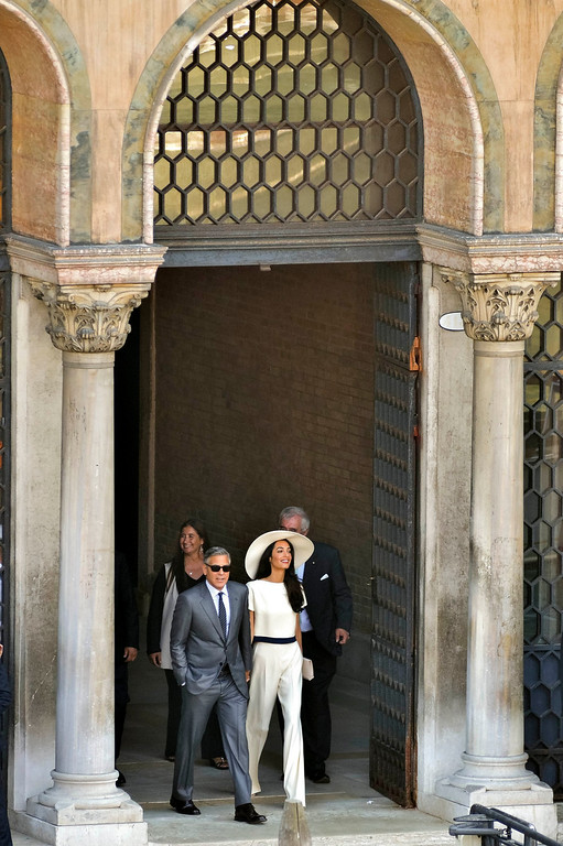 . Actor George Clooney, left, and his wife Amal Alamuddin leave the city hall in Venice, Italy, Monday, Sept. 29, 2014. George Clooney married human rights lawyer Amal Alamuddin Saturday, the actor\'s representative said, out of sight of pursuing paparazzi and adoring crowds. (AP Photo/Luigi Costantini)