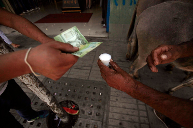 . In this Dec. 13, 2014 photo, Marco Alegria hands a customer a small cup of fresh donkey milk as the customer hands him money in the streets of Santiago, Chile. Selling donkey milk is a rare job, but a very old one. The ancient Greek physician Hippocrates recommended donkey\'s milk for some ailments and at least some claim that Cleopatra bathed in it for her skin.  (AP Photo/Luis Hidalgo)