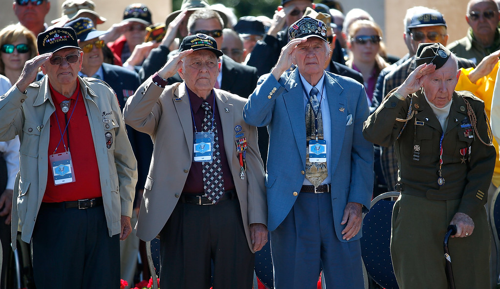 """. WWII Veterans salute during the playing of \""""Taps\"""" at a ceremony with U.S. President Barack Obama at the Normandy American Cemetery on the 70th anniversary of D-Day June 6, 2014 in Colleville-sur-Mer, France. June 6th is the 70th anniversary of the D-Day landings that saw 156,000 troops from the allied countries including the United States and the United Kingdom join forces to launch an attack on the beaches of Normandy, these assaults are credited with the eventual defeat of Nazi Germany.  (Photo by Win McNamee/Getty Images)"""