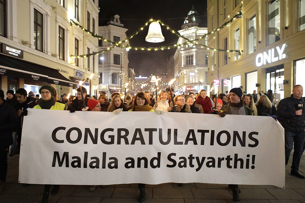 """. People hold a banner reading \""""congratulations Malala and Satyarthi\"""" during a torchlight procession before Nobel Peace Prize 2014 laureates Pakistan\'s Malala Yousafzai and India\'s Kailash Satyarthi wave from the balcony of the Grand Hotel ahead of the Nobel Banquet following the Nobel Peace Prize ceremony in Oslo on December 10, 2014. The 17-year-old Pakistani girls\' education activist Malala Yousafzai known as Malala shares the 2014 peace prize with the Indian campaigner Kailash Satyarthi, 60, who has fought for 35 years to free thousands of children from virtual slave labour.   AFP PHOTO / NTB SCANPIX / TORSTEIN BOE +++ NORWAY OUTTORSTEIN BOE/AFP/Getty Images"""