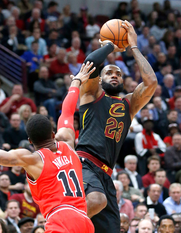 . Cleveland Cavaliers\' LeBron James, right, shoots over Chicago Bulls\' David Nwaba during the first half of an NBA basketball game Monday, Dec. 4, 2017, in Chicago. (AP Photo/Charles Rex Arbogast)