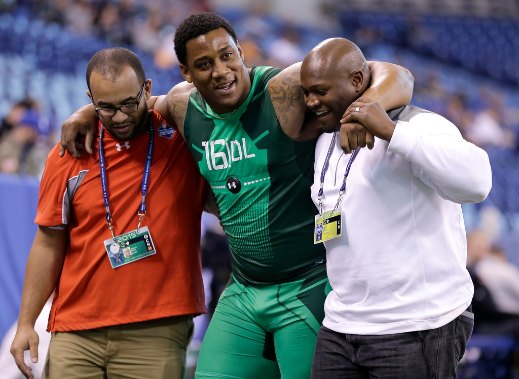 . Louisville defensive lineman B.J. Dubose, center, is helped by Dallas Cowboys scout Kevin Simon, right, and NFL Trainer Marcus Davis after he fell upon finishing the 40-yard dash at the NFL football scouting combine in Indianapolis, Sunday, Feb. 22, 2015. (AP Photo/Julio Cortez)