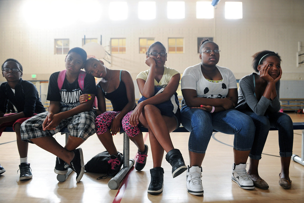 ". DENVER, CO - JULY 1:  From left to right; Dashawn Tolbert, 13, Jaisen White, 13, Kiyara Copney, 14, Tyra Goodluck, Davion Applewhite, 16 and Kimyara Gay-Blake, 14, watch a documentary on farming practices in the United States during a summer camp at St. Charles Recreation Center at 3777 Lafayette Street in Denver, CO. on July 1, 2013.  DJ Cavem Moetavation and his wife Neambe Leadon Vita, not shown, hold the camp to introduce kids to healthy eating habits, teach them about organic farming and changing the way they think about food. They also make organic juice during the day using produce from the couple\'s garden which includes cucumbers, strawberries, watermelon, kale, lime and coconut water.   As part of our ""Summer of Love\"" series for the Style section we profile the relationship of DJ Cavem Moetavation (a.k.a. Ietef Vita) and his wife Neambe Vita.  They are proud and longtime Five Points residents. They\'re artists, community activists, musicians, teachers and more.  They espouse the idea of being vegan or vegetarian and promote eating healthfully and organically.  (Photo by Helen H. Richardson/The Denver Post)"