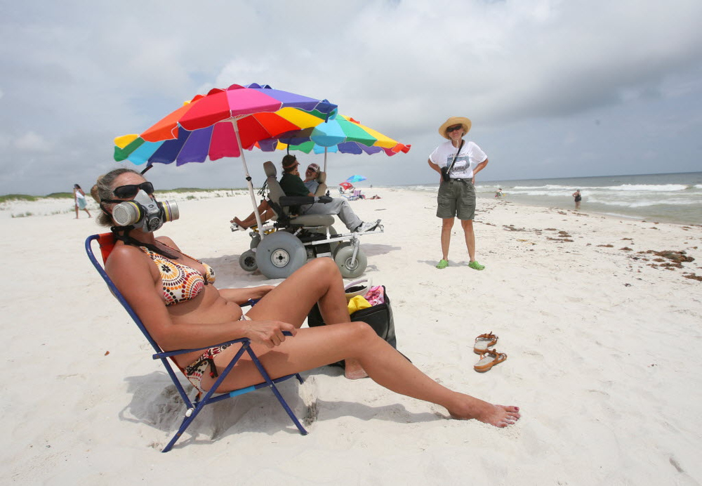 Description of . Sonja Daniel, who has a house on the Fort Morgan Peninsula, wears a mask Sunday, June 6, 2010 as she sunbathes on the beach of the Bon Secour National Wildlife Refuge in Baldwin County, Ala. Cleanup crews were working Sunday to remove tar balls and oily patches from the shoreline as managers at the refuge readied plans to construct dunes and berms to protect sensitive lagoons and wetlands. (AP Photo/Mobile Press Register, Kate Mercer)