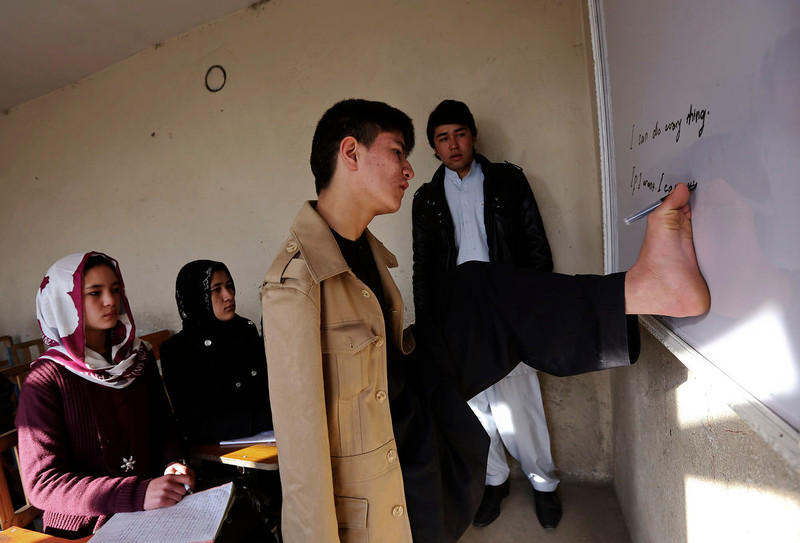 . Abbas Karimi, 14, who was born with no arms, writes with his foot at a classroom in Kabul February 18, 2013. Karimi has ambitions to earn a gold medal for his country in the world Paralympic games. If he gets the support he needs, the teenager will be the first Afghan to represent his county as a swimmer in the games next due to take place in Brazil in 2014. REUTERS/Omar Sobhani