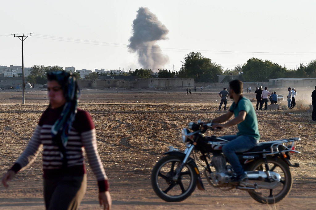 . Kurdish people wach air strikes at the Syrian town of Ain al-Arab, known as Kobane by the Kurds, as seen from the Turkish-Syrian border during heavy fighting, in the southeastern town of Suruc, Sanliurfa province, on October 7, 2014.  Fresh air strikes by the US-led coalition hit positions held by Islamic State jihadists in the southwest of the key Syrian border town of Ain al-Arab (Kobane), according to an AFP journalist just across the border in Turkey. The strikes came a day after the extremists pushed into Kobane, seizing three districts in the city\'s east after fierce street battles with its Kurdish defenders. ARIS MESSINIS/AFP/Getty Images