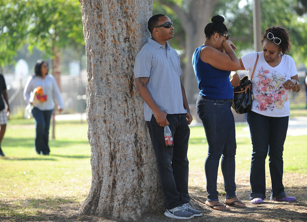 . Long Beach, Calif., -- 10-12-13- George Taylor near the scene where his mother  Kellye Taylor,53, was fatally  stabbed in front of her students, at Orizaba Park  Friday October 11th 2013, in Long Beach Calif. Pastor Gregory Sanders,left, leads the prayer.     Stephen Carr/  Daily Breeze