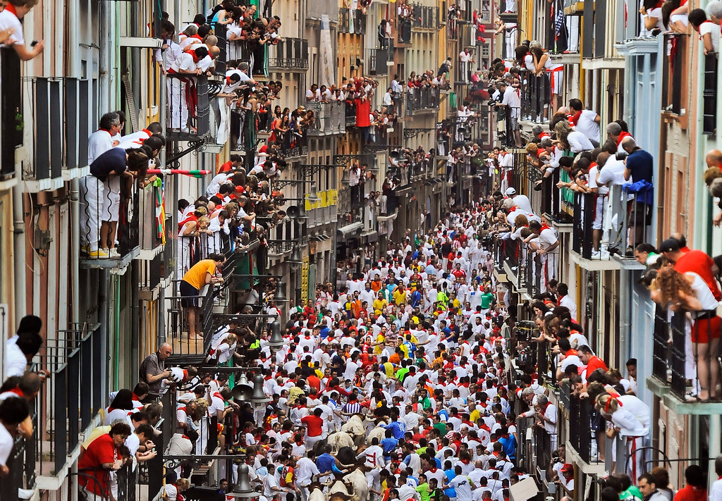 ". Runners make their way through the street with ""El Pilar\"" fighting bulls watched by people from their balconies during the running of the bulls at the San Fermin festival, in Pamplona, Spain, Friday, July 12, 2013. Revelers from around the world arrive to Pamplona every year to take part in some of the eight days of the running of the bulls glorified by Ernest Hemingway\'s 1926 novel \""The Sun Also Rises.\"" (AP Photo/Alvaro Barrientos)"