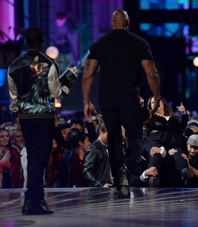 . Melissa McCarthy, background right,  crowd surfs toward the stage before accepting the comedic genius award at the MTV Movie Awards at Warner Bros. Studio on Saturday, April 9, 2016, in Burbank, Calif. Waiting on stage for her are presenters Kevin Hart, left, and Dwayne Johnson. (Kevork Djansezian/Pool Photo via AP)