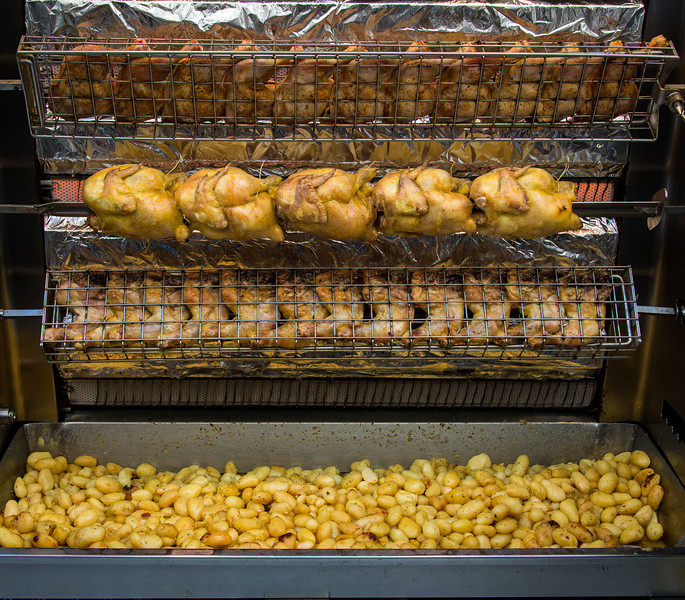 Street-front riches. The drippings from the revolving roasting poultry rain down upon the potatoes in the bin...a match made in spit-fired heaven!