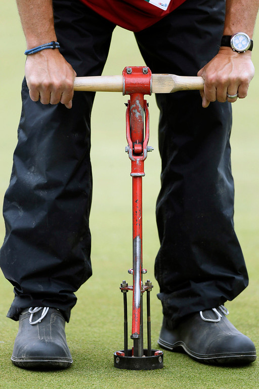 . Course worker Mark Wennemer drills a hole on the seventh green during the first round of the U.S. Open golf tournament at Merion Golf Club, Thursday, June 13, 2013, in Ardmore, Pa. (AP Photo/Julio Cortez)