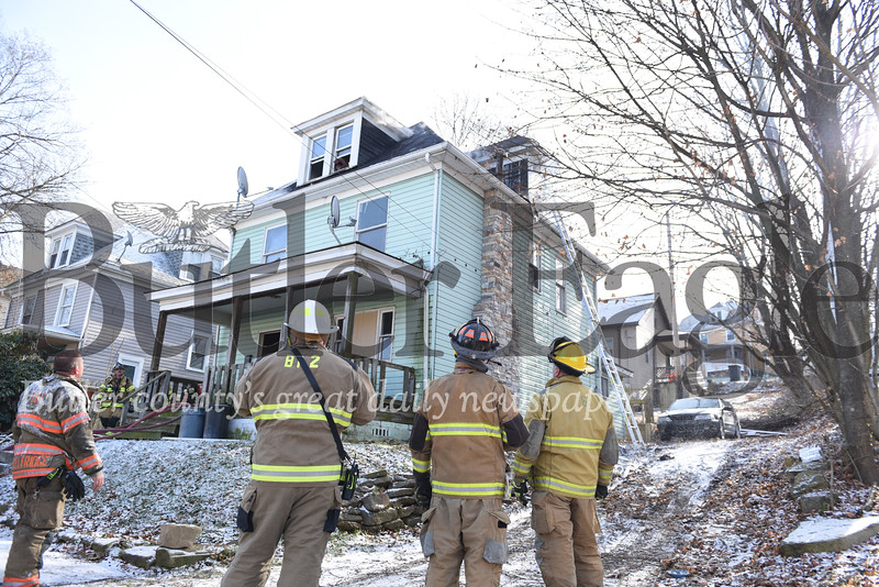 Firefighters stand outside a home on South Street in Butler where a fire and smoke was coming out of the attic Thursday afternoon.