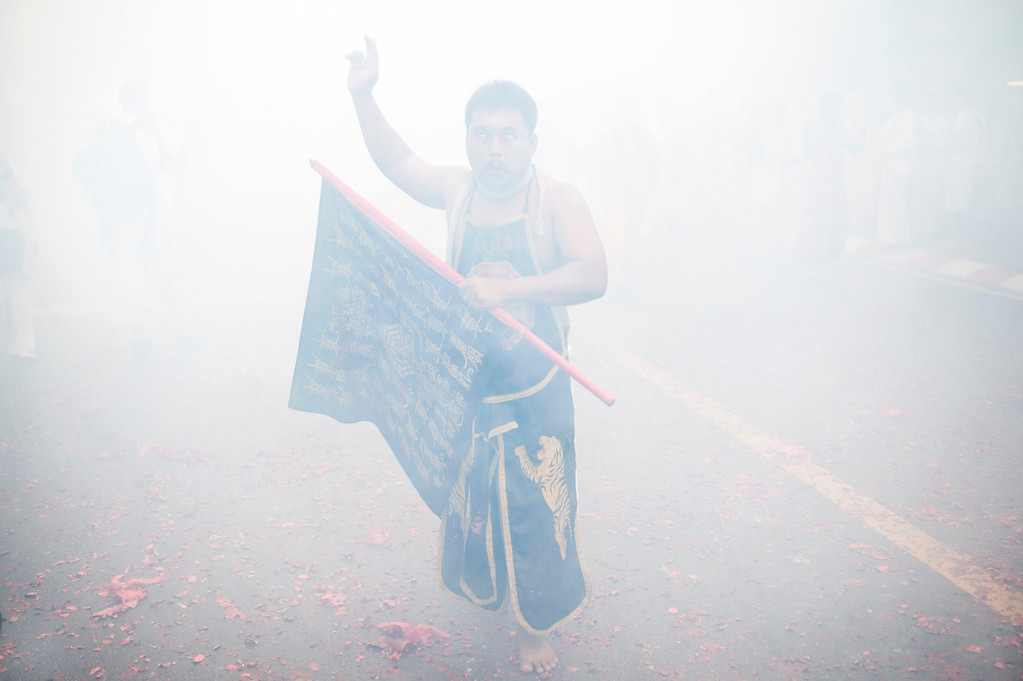 . Vegetarian festival devotee of Jui Tui shrine parades through the streets as firecrackers go off on September 30, 2014 in Phuket, Thailand. (Photo by Borja Sanchez-Trillo/Getty Images)