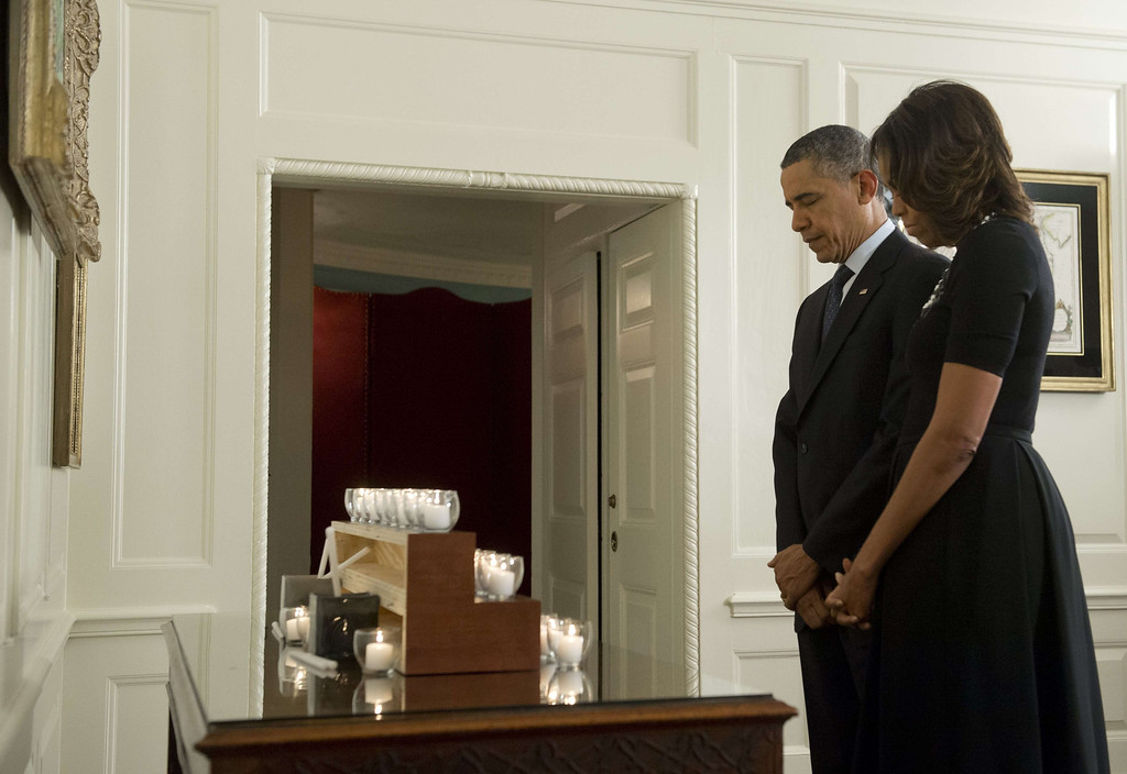 . US President Barack Obama and First Lady Michelle Obama observe a moment of silence, honoring the 26 students and teachers killed at Sandy Hook Elementary School in Newtown, Connecticut, in the Map Rom of the White House in Washington, DC on December 14, 2013. The Obamas also lit 26 candles on the one-year anniversary of the shooting.    AFP PHOTO / Saul LOEB/AFP/Getty Images