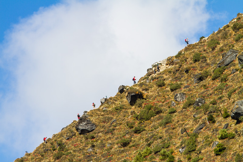 Trekkers in Nepal's Himalayas are seen along an uphill ridgeline against a sky of blue and a large white cloud