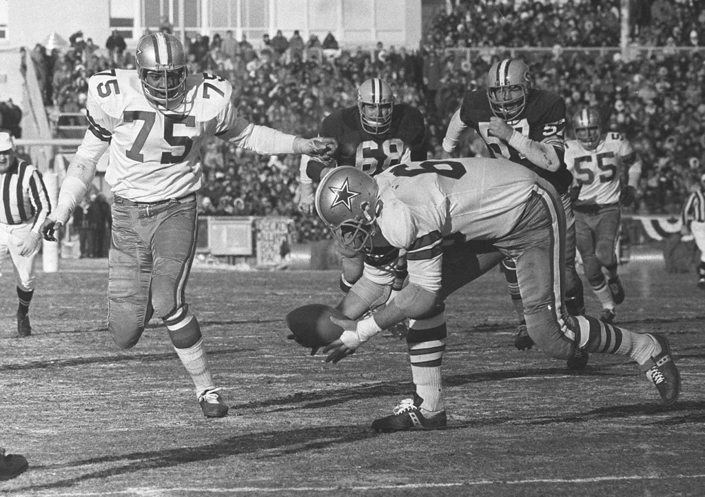 . Dallas Cowboys defensive end George Andrie picks up a Bart Starr fumble and is about to follow teammate Jethro Pugh (75) into the end zone to score in the NFL Championship game against the Green Bay Packers, Dec. 31, 1967.  This game took place in Green Bay, Wis.  Played in sub-zero temperatures the contest was later dubbed \'The Ice Bowl.\'  (AP Photo/files)