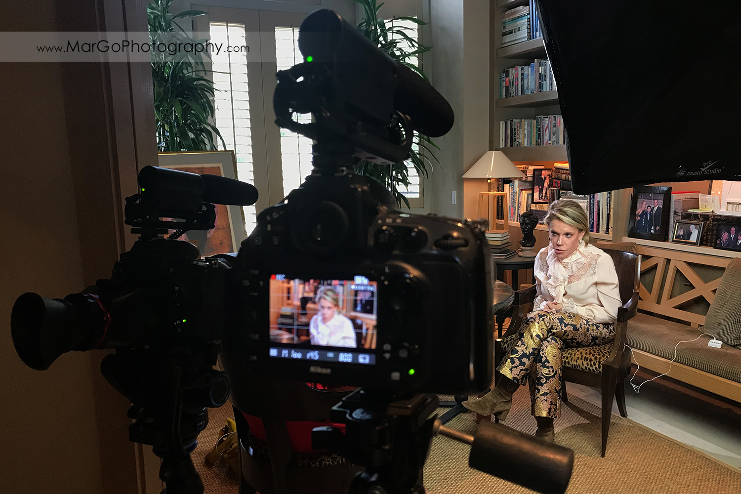 women interviewed at her library seen through two camera interview setup