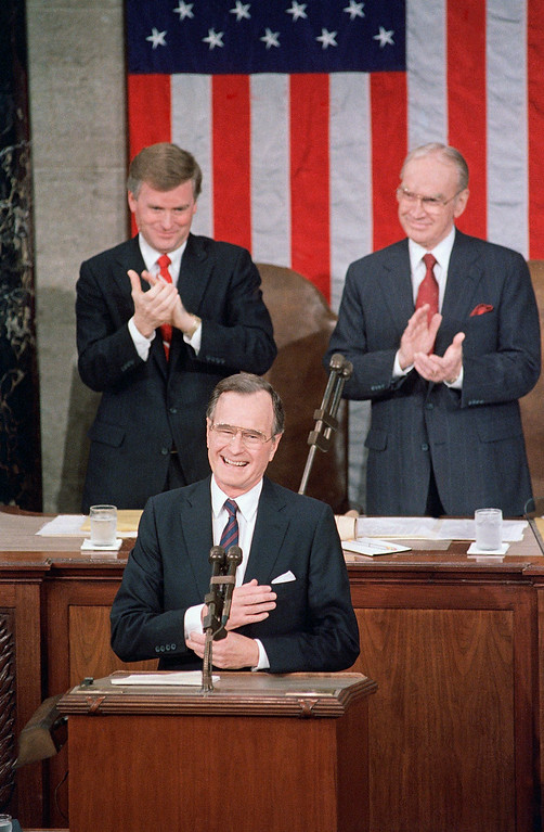 . Pres. George H. W. Bush, front, acknowledges applause before addressing a Joint Session of Congress at the Capitol, Thursday, Feb. 9, 1989, Washington, D.C. Behind are Vice Pres. Dan Quayle and House Speaker Jim Wright. (AP Photo/Bob Daugherty)